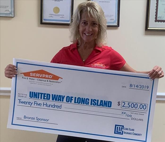 female employee holding a $2500 check donation