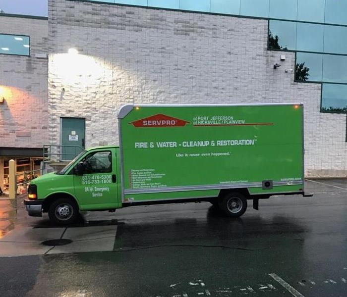 SERVPRO truck parked in front of a flood damaged commercial facility