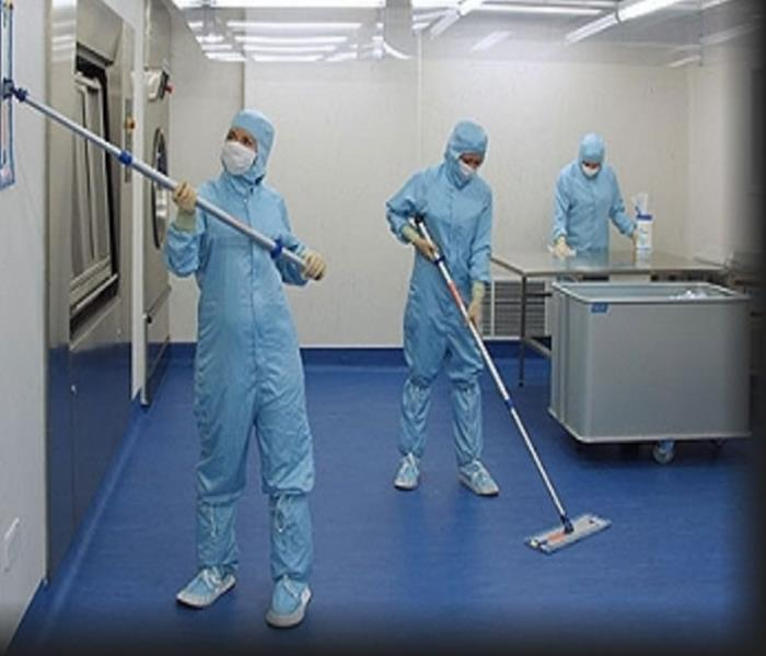 Technicians in Personal Protective Equipment Cleaning in a hospital operating room